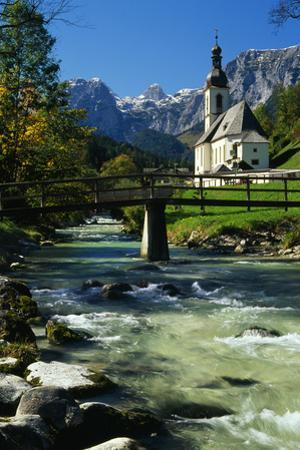 Snow dusted mountain peaks above a valley with church and river. by Norbert Rosing