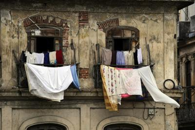 Laundry hanging from the balcony of an old building. by O. Louis Mazzatenta