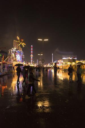 https://imgc.allpostersimages.com/img/posters/oktoberfest-wiesn-by-night-lights-in-the-rain_u-L-Q1EYEJ00.jpg?artPerspective=n