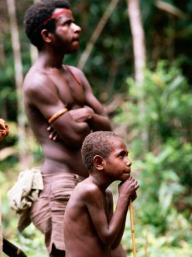 Man and Boy Watching Work, Oriomo Plateau, Western, Papua New Guinea by Oliver Strewe
