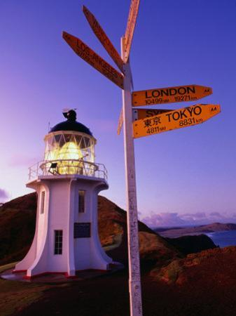 Signpost in Front of Lighthouse at Dawn, Cape Reinga, New Zealand by Oliver Strewe