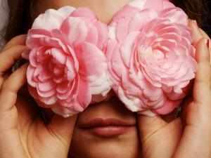 Young Girl Holding Camellia Flowers over Her Eyes by Oliver Strewe