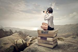 Beautiful Woman Sitting On A Pile Of Old Books Watching With Binoculars by olly2