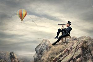 Rich Businessman Sitting On A Chair In The Mountain Looking The Landscape With Spyglass by olly2