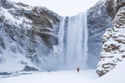 https://imgc.allpostersimages.com/img/posters/one-person-in-red-jacket-walking-in-the-snow-towards-skogafoss-waterfall-in-winter_u-L-PWFJVF0.jpg?p=0