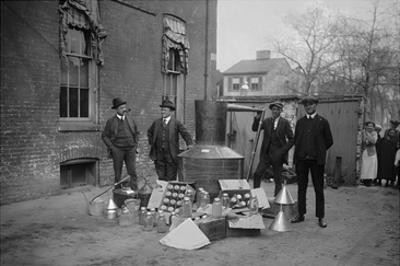 Onlookers Watch as Suited Men Stand in Front of a Large Copper Kettle for Making Illegal Liquor