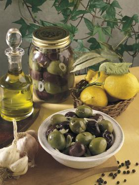 Close-Up of Olives with Garlic and a Bottle of Olive Oil by P. Martini