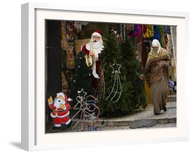 Palestinian Woman Walks Past Christmas Decorations at a Shop in Jerusalem's Old City