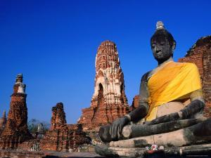 Buddha Statue in Yellow Silk with Ruins in Background by Paolo Cordelli