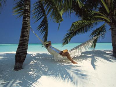 Man Relaxing on a Beachside Hammock, Maldives, Indian Ocean