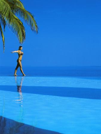 Woman Balancing on Edge of Infinity Pool, Maldives, Indian Ocean