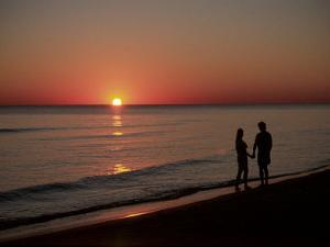 Silhouette of Couple on Beach at Sunset, FL by Pat Canova
