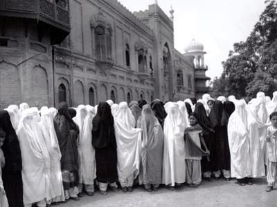 Pathan Women Observe Strict Muslim Purdah as They Come out to Vote at a High School