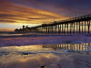 A Lone Surfer Waits for a Wave a People Stroll the Pier Watching a Brilliant Sunset, Oceanside by Patrick Smith