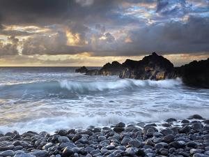 Waves Battering Shore Rocks and Black Cobblestones on a Beach Near Hana, Maui, USA by Patrick Smith