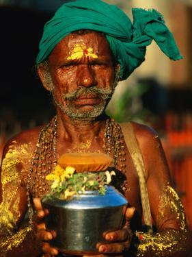 Pilgrim with Offerings to Give to Deities at Sri Meenakshi Temple, Madurai, India by Paul Beinssen