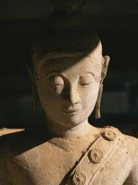 A Statue of Buddha with Eyes Shut Stands in Half Shadow by Paul Chesley