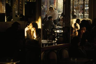 An interior scene in a cafe with sunset light streaming in. by Paul Chesley