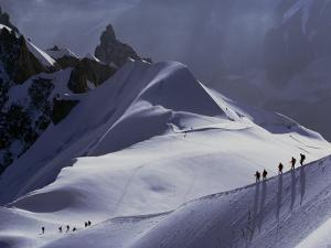 Hikers Follow a Path Across a Snow Field in the French Alps by Paul Chesley