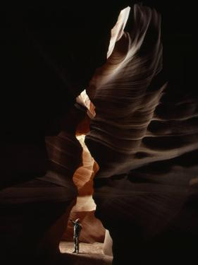 Man Standing in Sunlight in a Narrow Slot Canyon by Paul Chesley