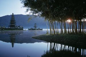 Misty lake with shrine, Bali Island, Indonesia. by Paul Chesley
