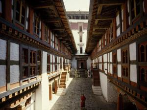 Monk Walks Through the Fortress-Style Architecture of a Dzong by Paul Chesley