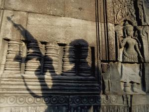 The Silhouetted Shadow of a Man Holding an Automatic Rifle is Cast against a Cambodian Temple Wall by Paul Chesley