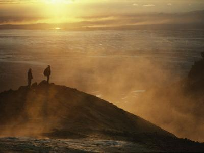 Two Silhouetted Men at Twilight Amid Geothermal Steam on Mountain Top by Paul Chesley