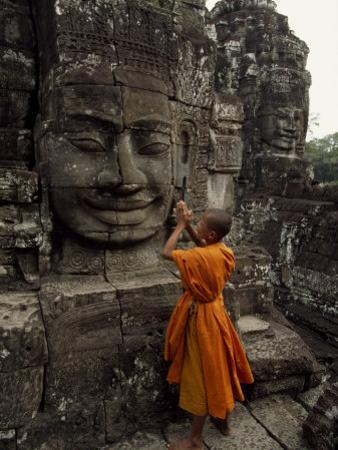 Young Buddhist Monk Prays at a Relief Statue of Buddha by Paul Chesley