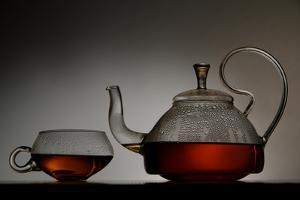 A Clear Glass Tea Pot Full of Hot Tea Sits Next to a Clear Glass Tea Cup with Tea by Paul Damien