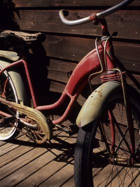 A Very Old Red Girls' Bike Rests on an Old Wooden Porch by Paul Damien