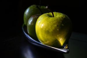 Close Up of Three Wet Green Apples in a Dish by Paul Damien