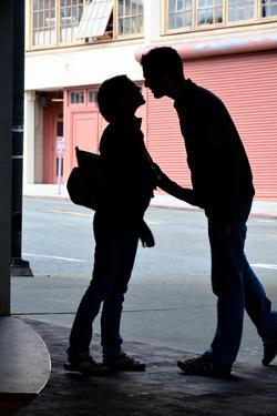 Silhouette of Young Engaged Couple Bending Forward for a Kiss by Paul Damien