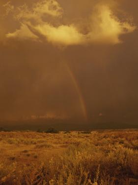 Storm Clouds and a Rainbow Appear over the Prairie Landscape by Paul Damien
