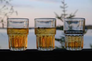 Three Glasses of Brandy Old Fashions on the Railing of a Wooden Deck by Paul Damien