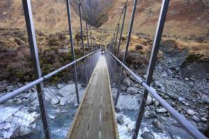 A Long Suspension Bridge over a River on the Fox Glacier Track, Wanaka, South Island, New Zealand by Paul Dymond
