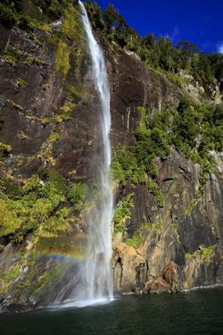A Tall Waterfall Drops Off a Steep Cliff into Waters, Milford Sound on South Island, New Zealand by Paul Dymond