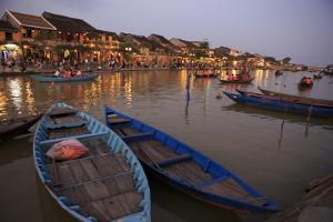 Boats moored on the Thu Bon River opposite Bach Dang Street in the old town of Hoi An, Vietnam by Paul Dymond
