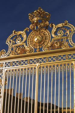 The ornate golden entrance gates to the Chateau Versailles on the outskirts of Paris, France by Paul Dymond
