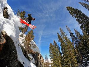 Skier Jumping Off Small Cliff at Brighton Ski Resort by Paul Kennedy