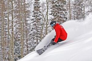 Snowboarder Enjoying Deep Fresh Powder at Brighton Ski Resort. by Paul Kennedy