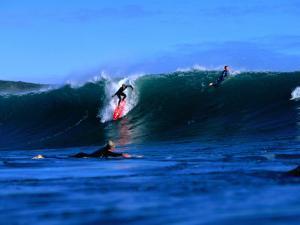 Surfers in Manu Bay, New Zealand by Paul Kennedy