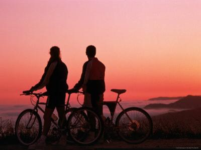 Silhouette of Two Cyclists at Sunset by Paul Meyer