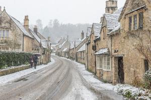 A couple walking up the hill in Castle Combe with an umbrella protecting them from the heavy snowfa by Paul Porter