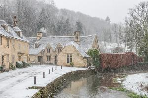 Snow covered houses by By Brook in Castle Combe with a dog enjoying a paddle, Wiltshire, England, U by Paul Porter