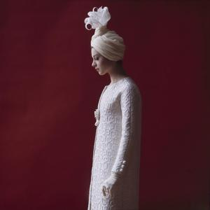 Model Dressed in a White Turban, Gloves, and Brocade Coat by Yves St Laurent, Paris, France, 1962 by Paul Schutzer