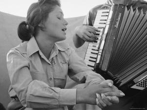 Young Israeli Woman Singing While Accompanied by Someone Playing an Accordion by Paul Schutzer
