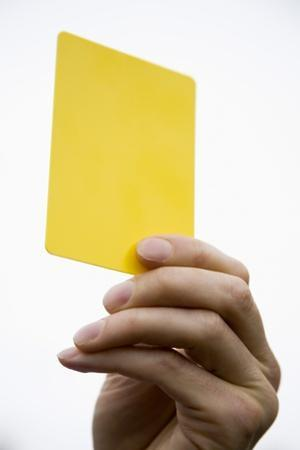 Hand Holding Yellow Card by Paul Seheult