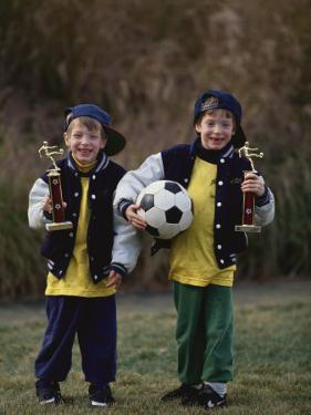 Two Young Brothers Posing with their Soccer Trophies by Paul Sutton