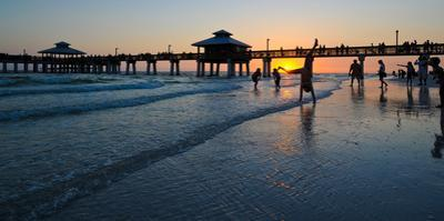 People and pier on Fort Myers Beach at sunset, Estero Island, Lee County, Florida, USA